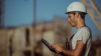 A construction worker wearing a hard out checks his iPad