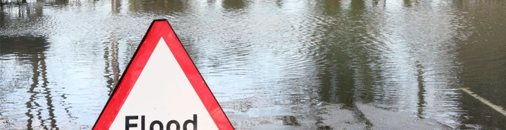 A flood warning sign erected on a water-logged road