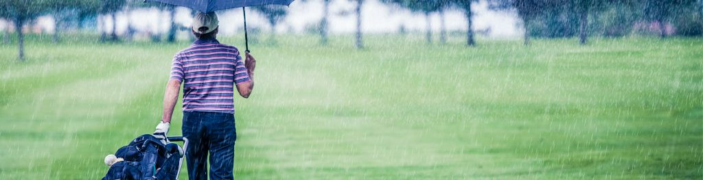A golfer holding an umbrella walks on a golf course in heavy rain.