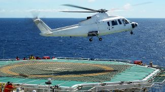A helicopter lands on the helipad of an oil platform in the North Sea.