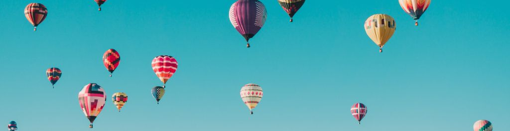 Hot air balloons sailing in a blue sky Photo Ian Dooley