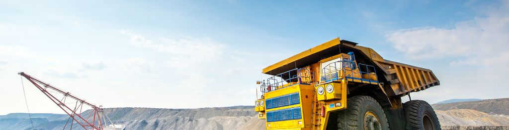 A big yellow mining truck in an opencast mine under a blue sky, and a crane in the background.