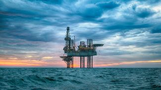 An offshore oil rig in blue choppy waters with a blue cloudy sky in the background