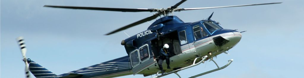 A blue and white police helicopter with an officer suspended in a harness by the door.
