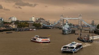 Muddy Thames busy with passenger ferries and a Navy frigate with Tower Bridge in the background, against an ochre-coloured sky