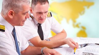 Two pilots planning over documents and charts.