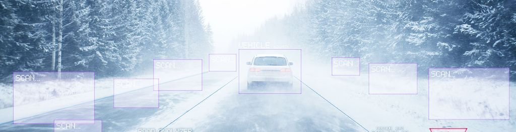 A car in motion in snowy and foggy conditions, viewed from a Connected and Autonomous Vehicle digital system displaying real-time weather data and a road surface analyser.