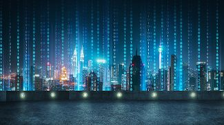 An illuminated night city skyline with vertical superimposed data symbols 0 and 1.
