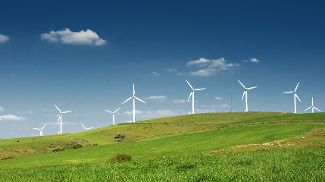 A wind farm in a green field against a blue sky with scattered clouds.