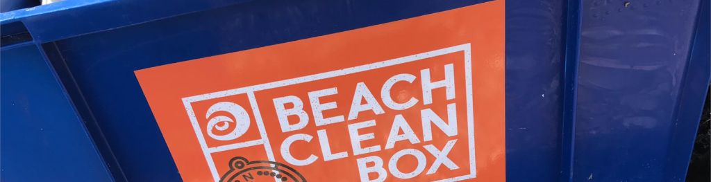A blue box used for beach cleaning from Surfers Against Sewage with a sticker on the side that reads 'Beach Clean Box'