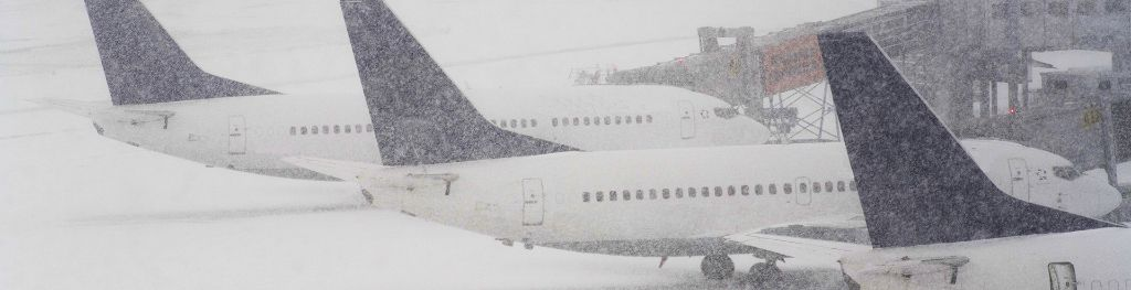 Three passenger aircrafts grounded at an airport due to snow.