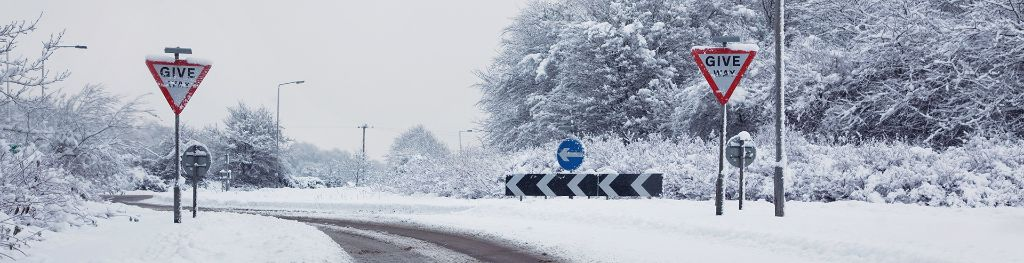 A snowy, bendy country road with traffic signs.