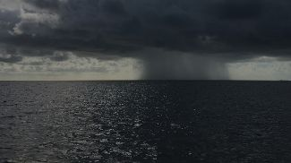 Rain falling on the horizon over the sea. Photo Brian Cook