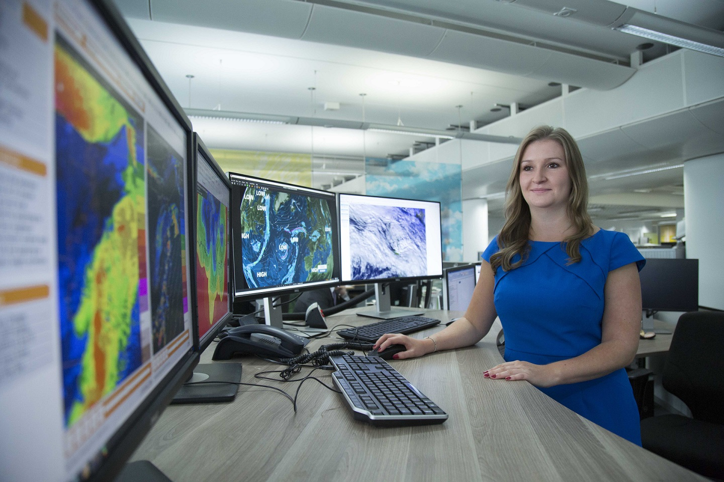A meteorologist working at their desk